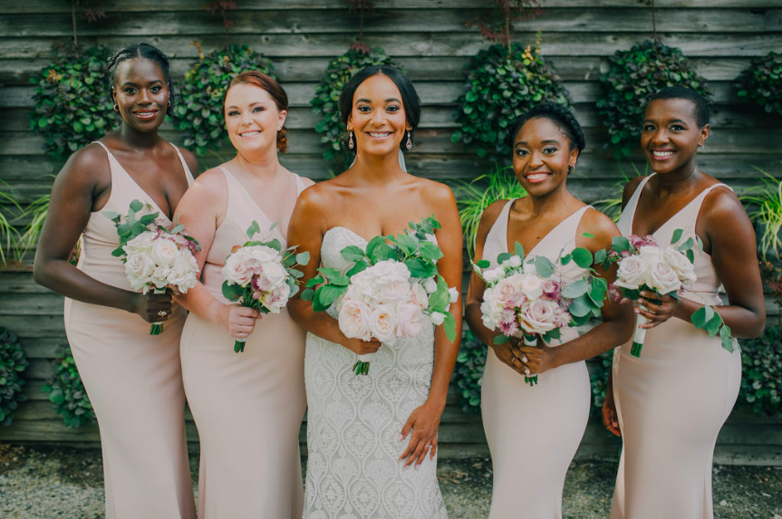 Bridal party wearing blush BHLDN gowns (Jones dress) and various hairstyles for straight, natural, and buzzcut looks. Bride is wearing boho wedding dress from BHLDN with thick lace overlay. Photo credit: Alex Medvick Photography