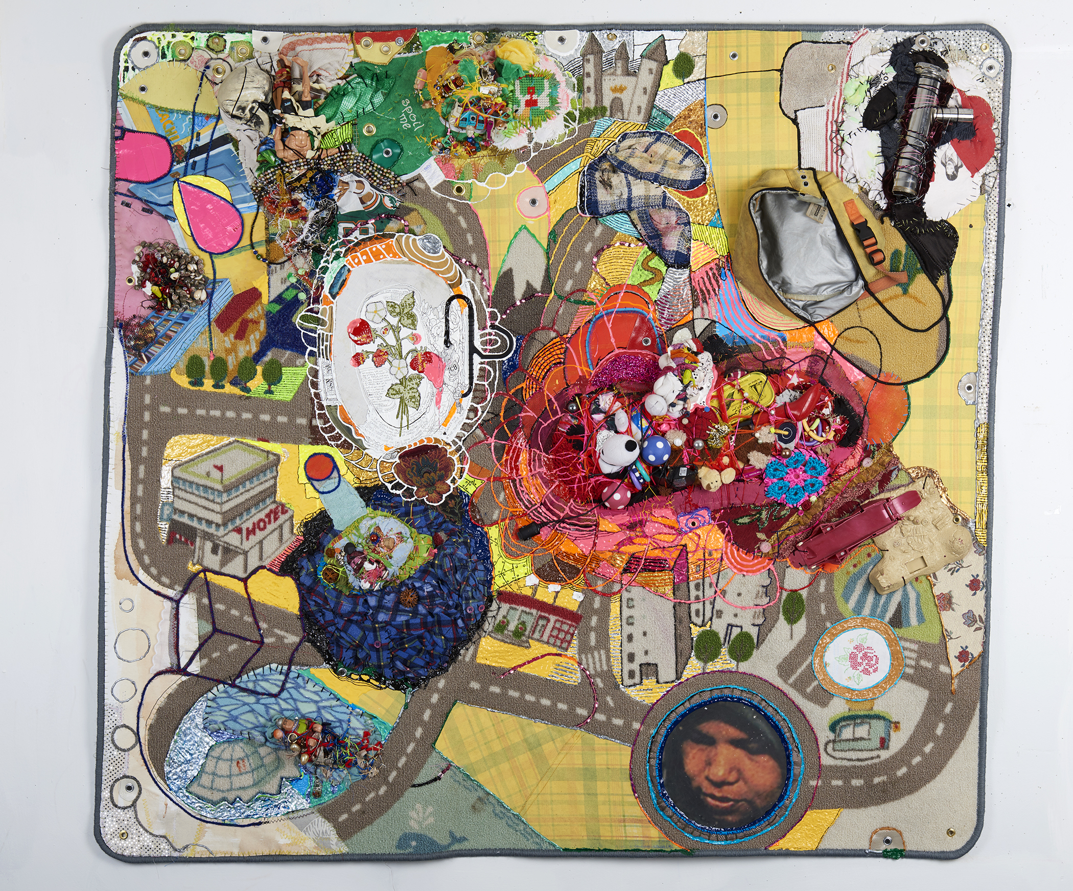 """Crawling on Cancer :      The Teflon Toxin by Sharon Lerner      2016,52""""x 55"""" x 6"""", trim, photo, resin, wood, thread, found objects, fabric paint, fabric, duct tape & grommets on my son's old Ikea carpet. Note: """"The Teflon Toxin"""" (known as C8) is found on most carpets and it is a carcinogen."""