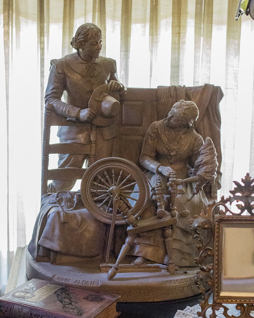 This was a statue of an older style of spinning wheel, complete with the wool being held on the distaff.  Note that she is reading a book on her lap as well.