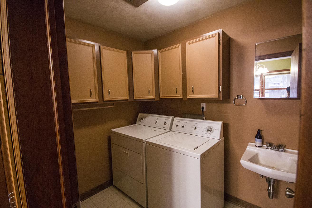 Changed: Brown paint for walls, dark brown paint for cabinets, brown paint for cabinet doors, new hinges and handles for cabinets, removal of sink hardware, washing machine and dryer, new light fixture.