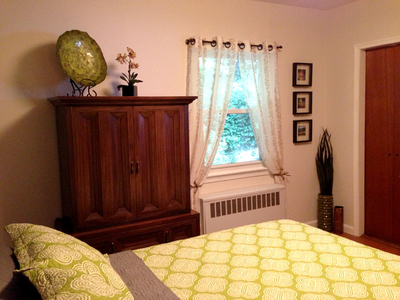 Instead, install tie-backs like these branch pulls to create a nice shape at the window area and now the radiator attracts less focus. The off-white hue with ivy detailing on these panels compliments the room and goes well with the new wall color.