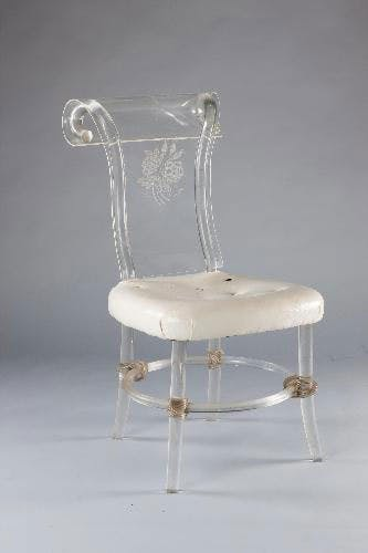 Early use of lucite in a curvaceous lucite and brass chair, circa 1930's.