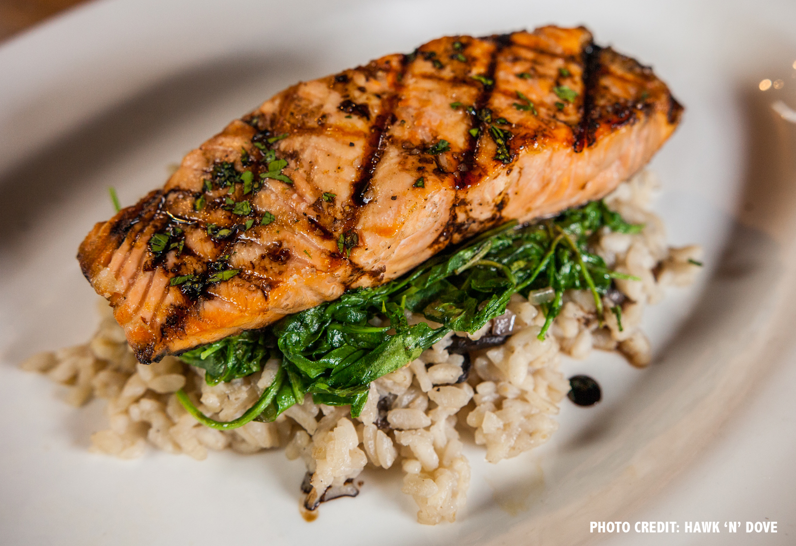 Grilled Atlantic salmon with mushroom risotto, wilted arugula and balsamic glaze.