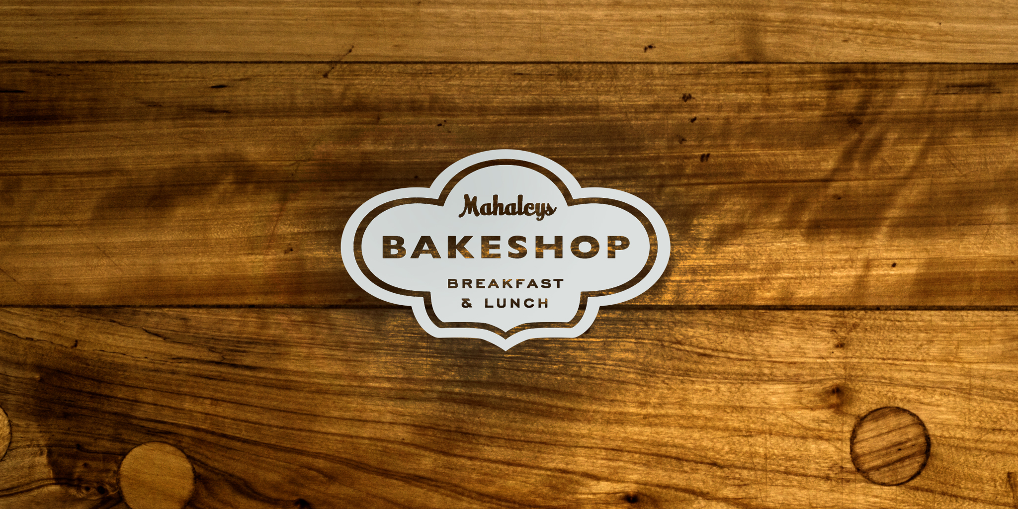 IDENTITY  Mahaley's Bakeshop  A small town appeal bakeshop needed a logo that sensibly revealed a warm and fuzzy emotion while conveying bakery. The puffy icon shape denoted both baked goods rising as well as a baker's hat.