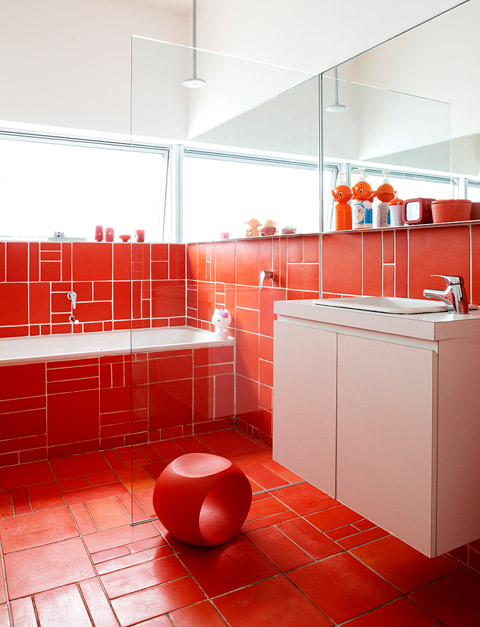 Dinosaur Designs homeware accessories and Japanese collectables dress the family's orange bathroom.