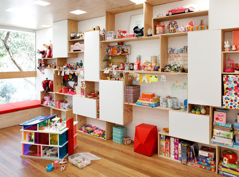 The joinery throughout the house was designed by Sam to store and display the family's collectables. In the playroom upstairs Lana and Scarlet make good use of the recycled plywood shelving.