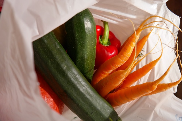 Plastic shopping bag containing red pepper, courgettes and carrots