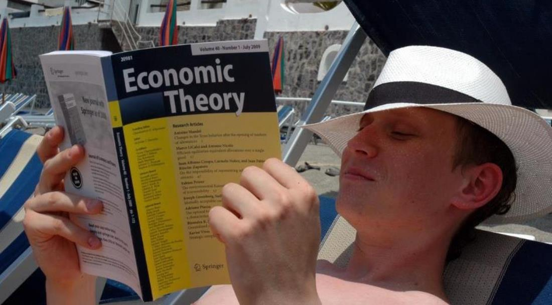 pawel, at the beach, casually reading a new york times best seller, faro, portugal, 2011