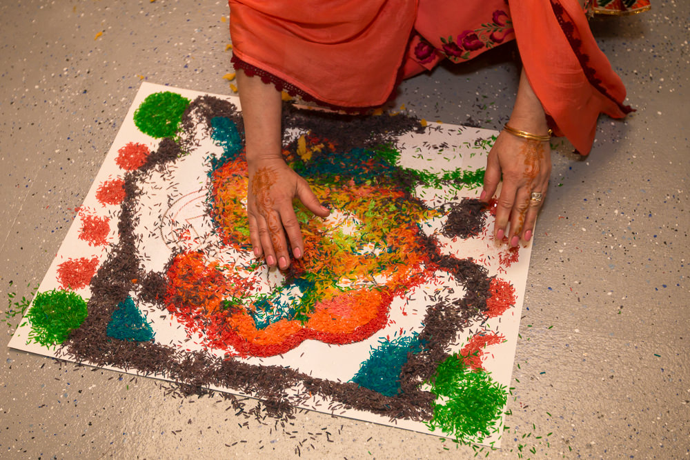 After the ceremony, Mom collects the colored rice and makes sure her wet hands got some stickings.