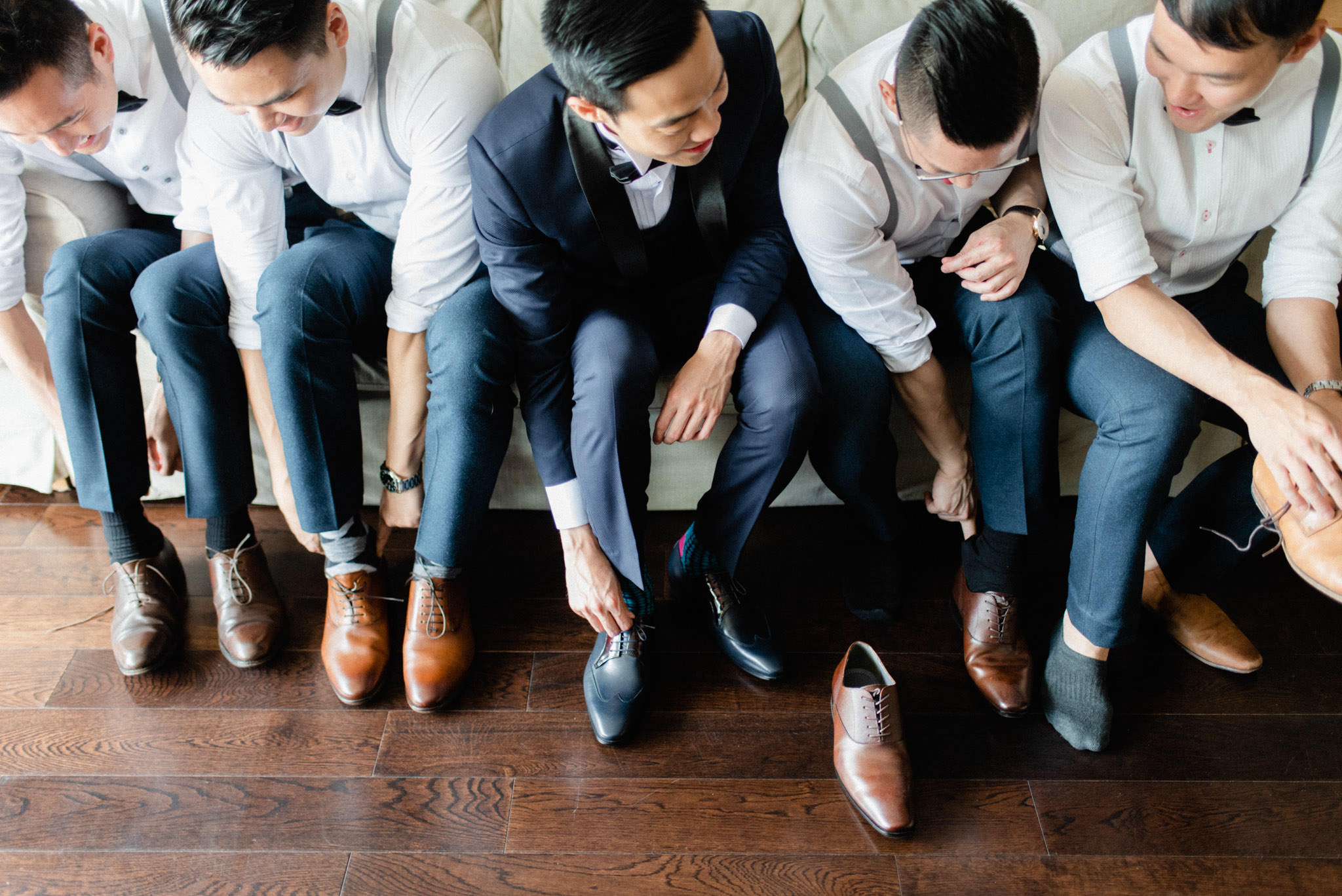 Groom and groomsmen putting on shoes