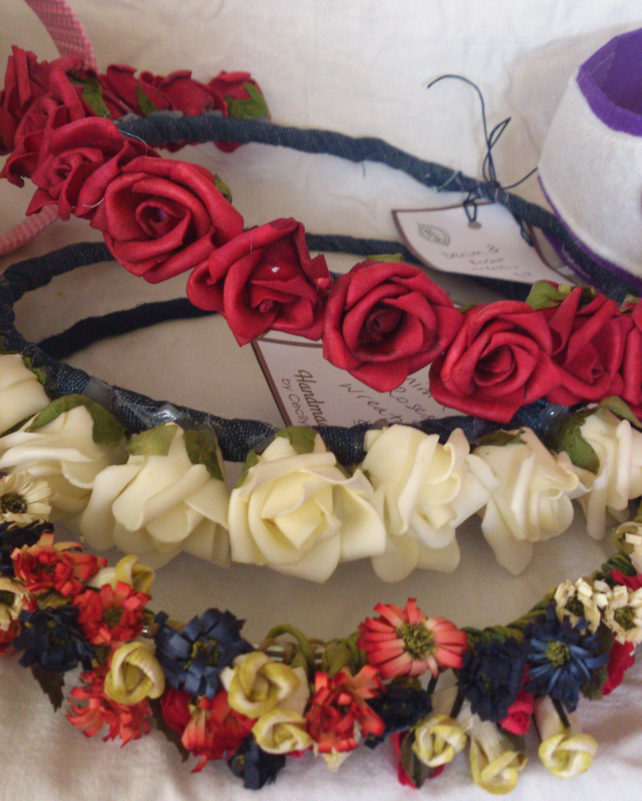 These flower wreaths were made with three rounds of heavy duty wire, wrapped around with denim strips. The roses were hot glued to the denim and the smaller flowers were wound around the binding and then hot glue finished.