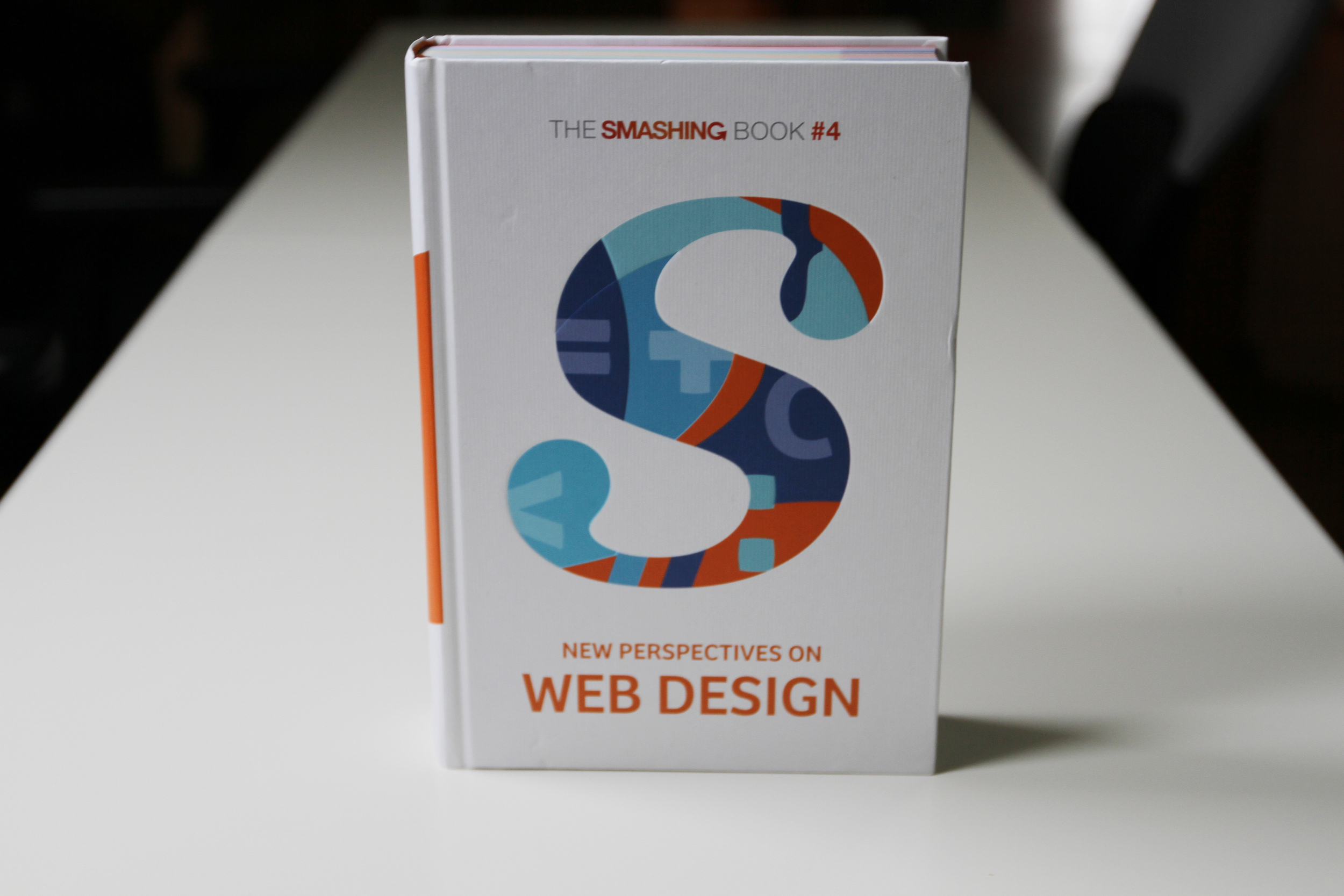 """The front cover for the new book features the Smashing """"S"""" filled with code symbols highlighting this edition's theme."""
