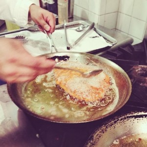 Basting a fried cutlet to achieve the perfect golden brown crust.