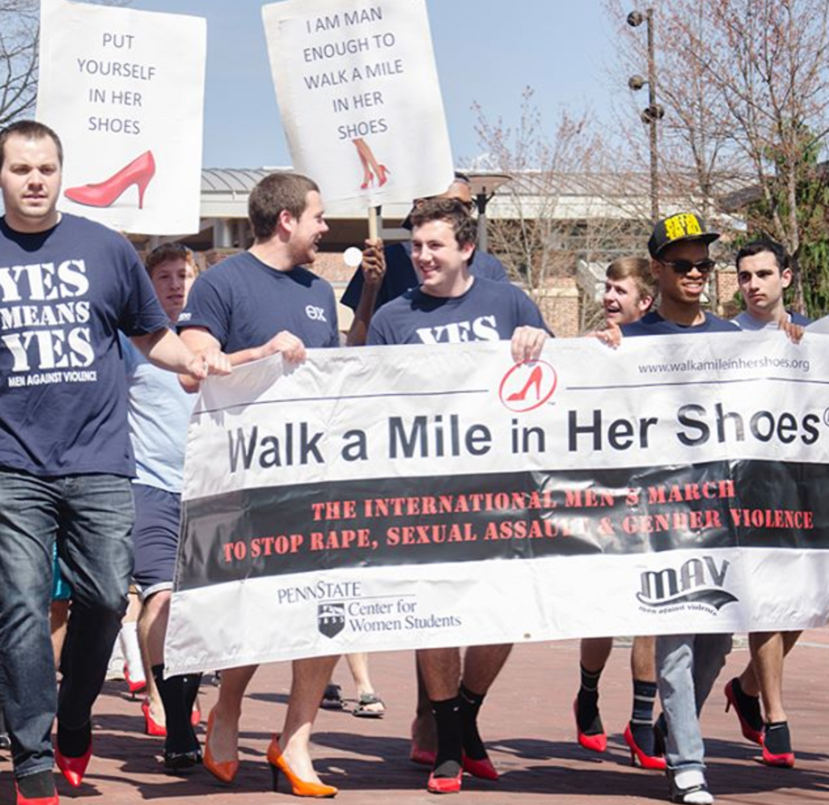 "Brothers John Broderick and Ryan Gattoni leading the ""Walk a Mile in her Shoes"" event with many Theta Chi brothers behind them."