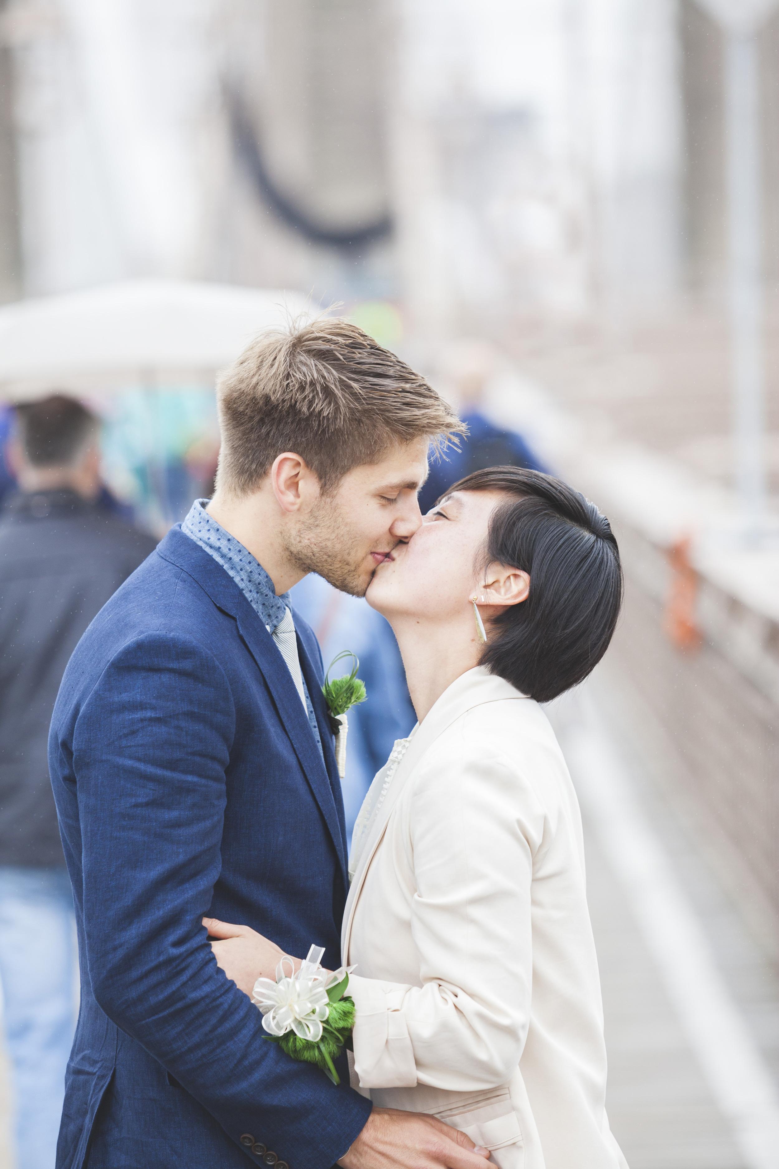 A wedding couple kiss on the Brooklyn Bridge.