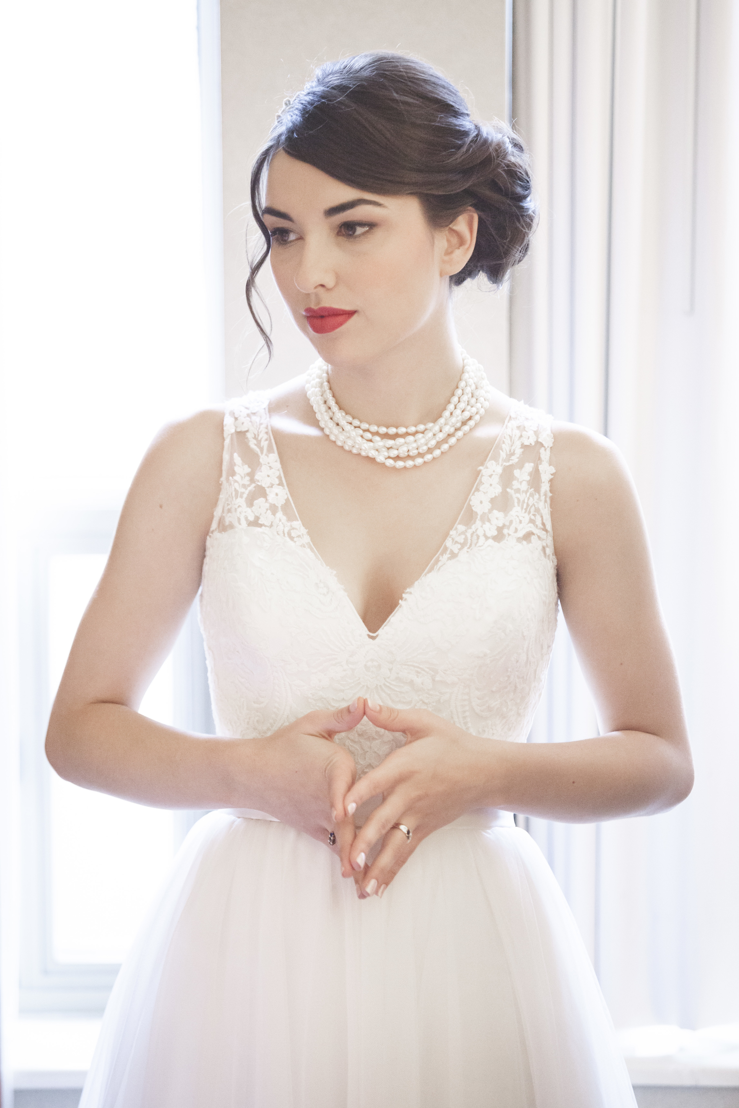 Bride in white dress by window