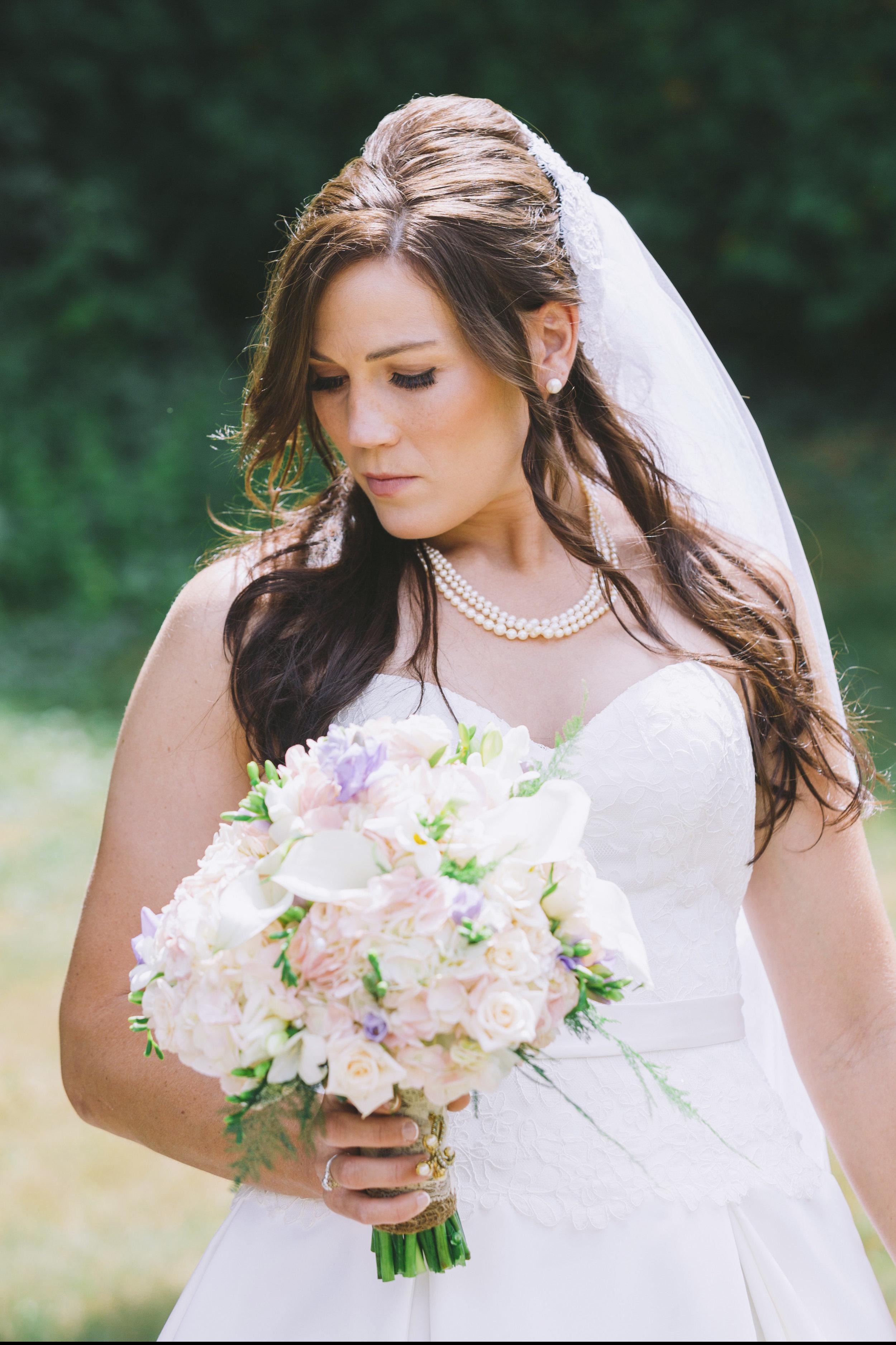 Bride protrait photo showing off bouquet of flowers