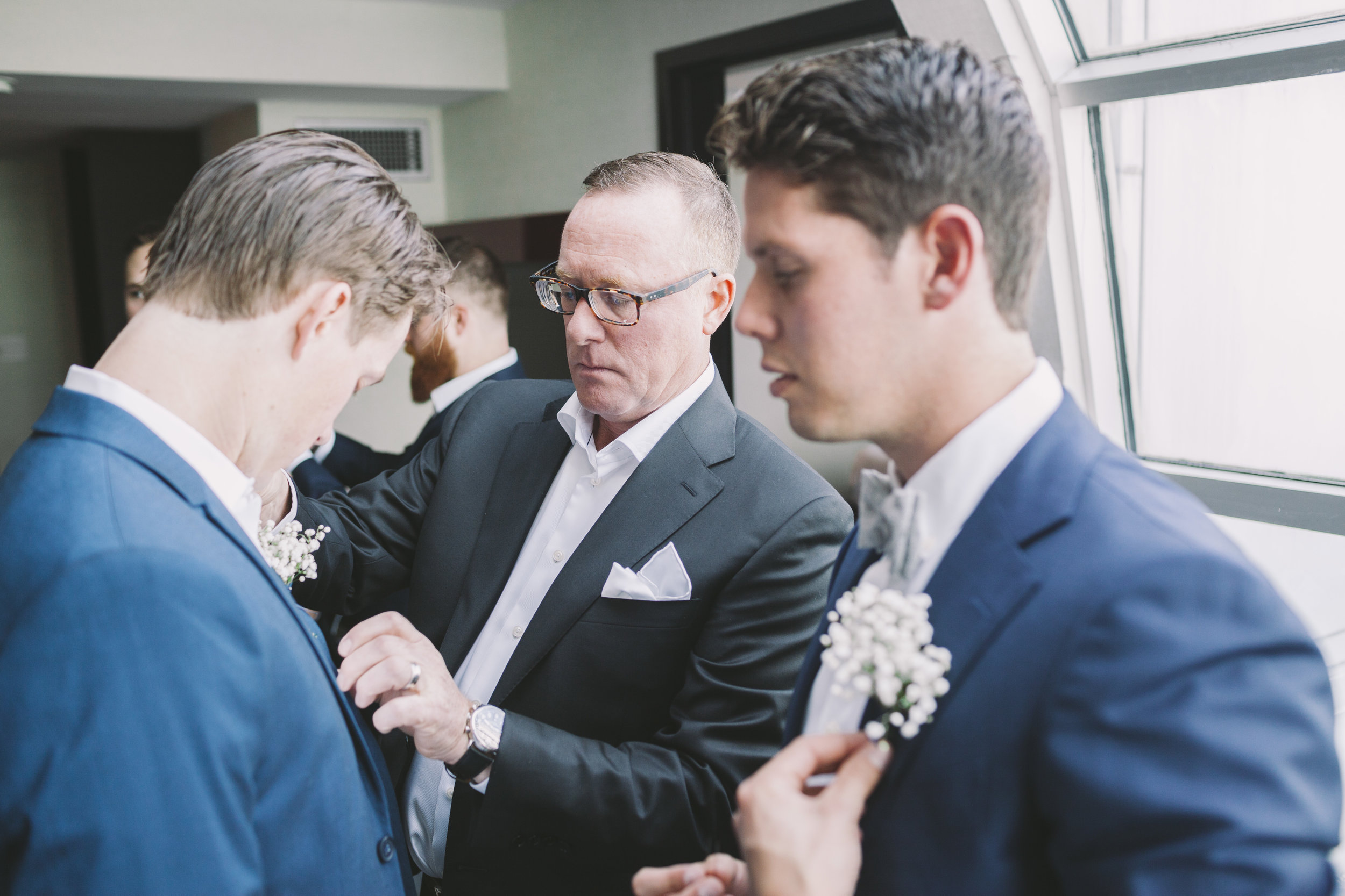 Groom putting on boutonniere.