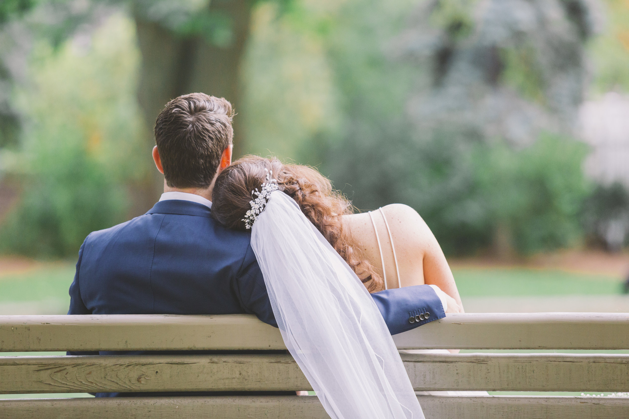 Wedding couple relaxing on a park bench.