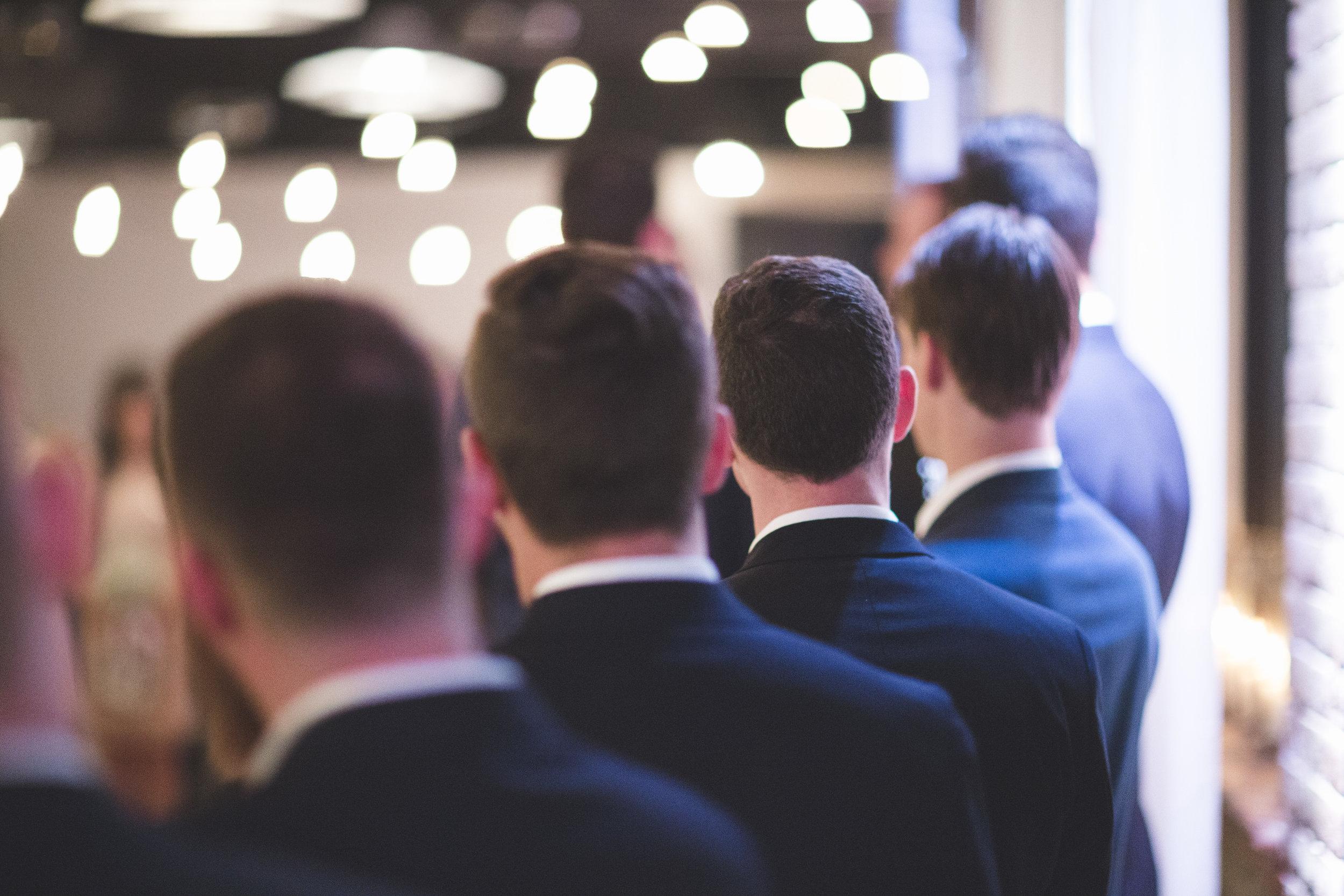 Groomsmen watching the wedding ceremony.