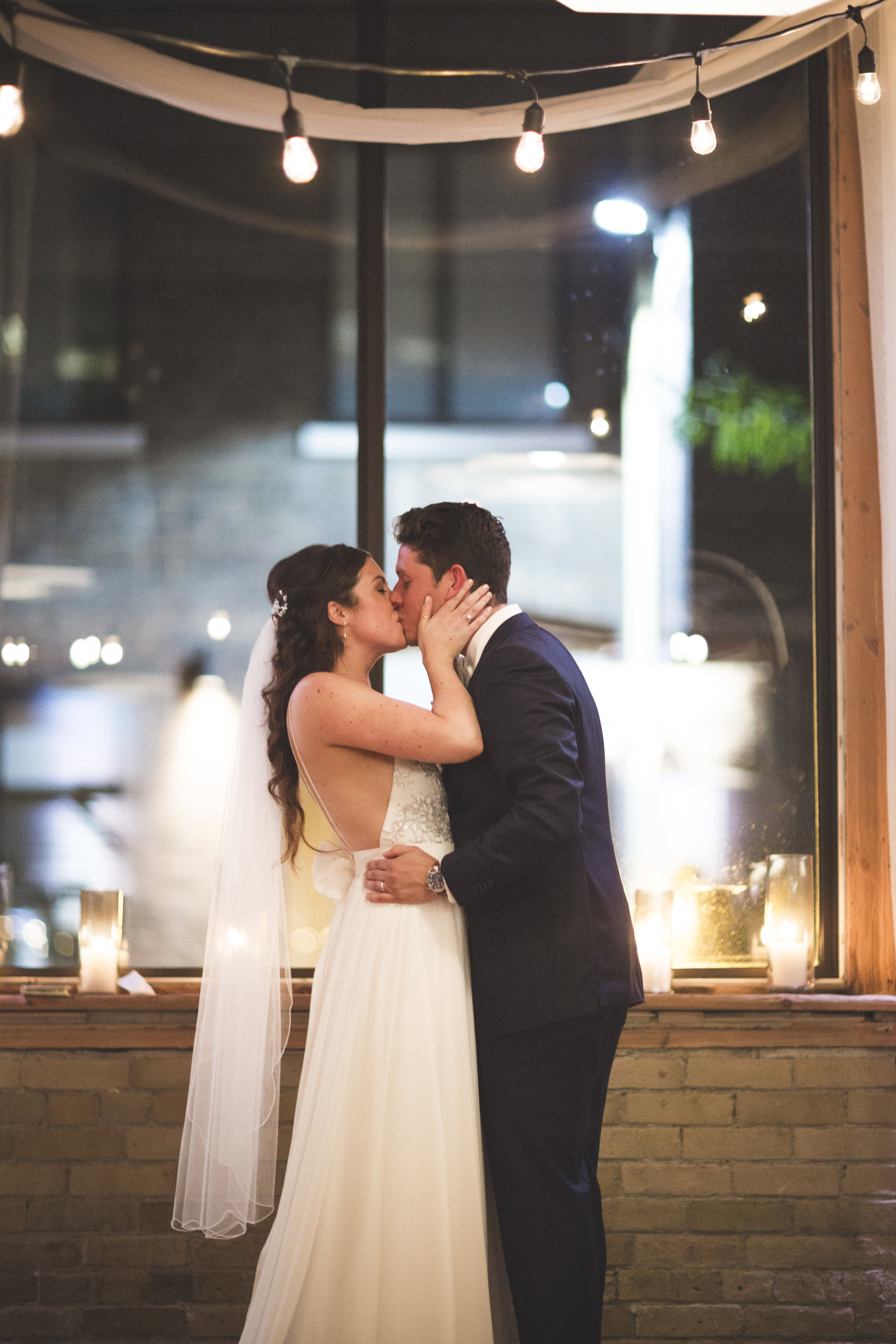 Bride and groom kissing under the lights at 2nd Floor Events in Toronto.