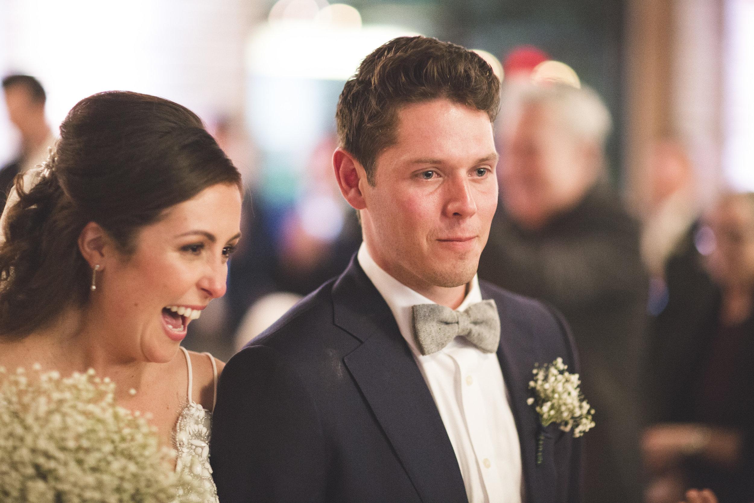 Emotional groom walking back down the aisle at wedding.