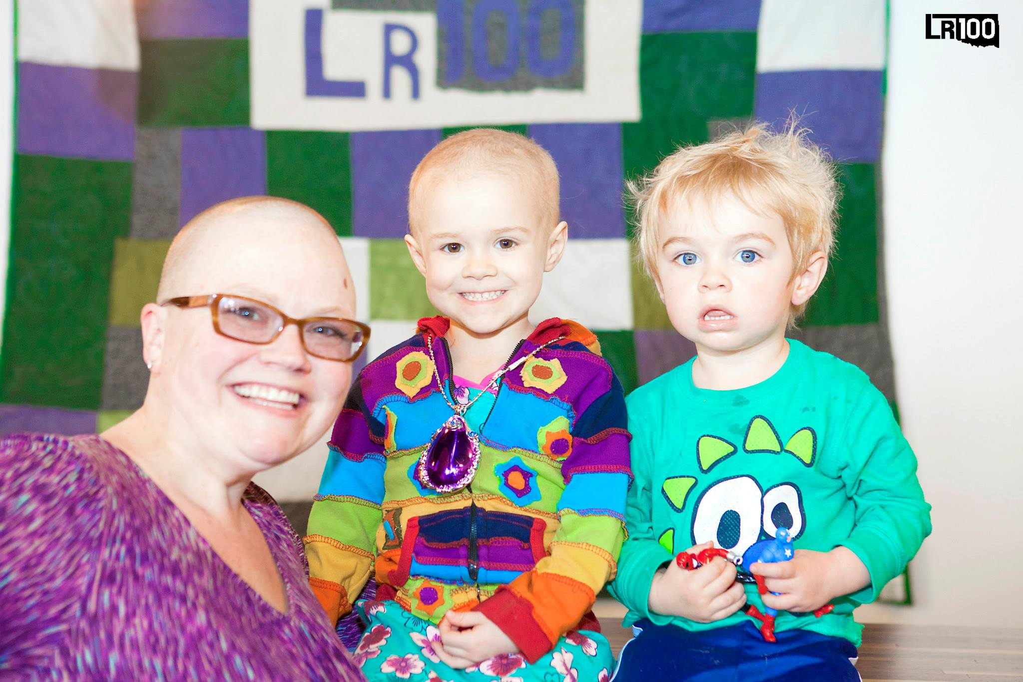 Andrea, Ainsley, and George with Andrea's LR100 quilt. Photo credit  241photography.com