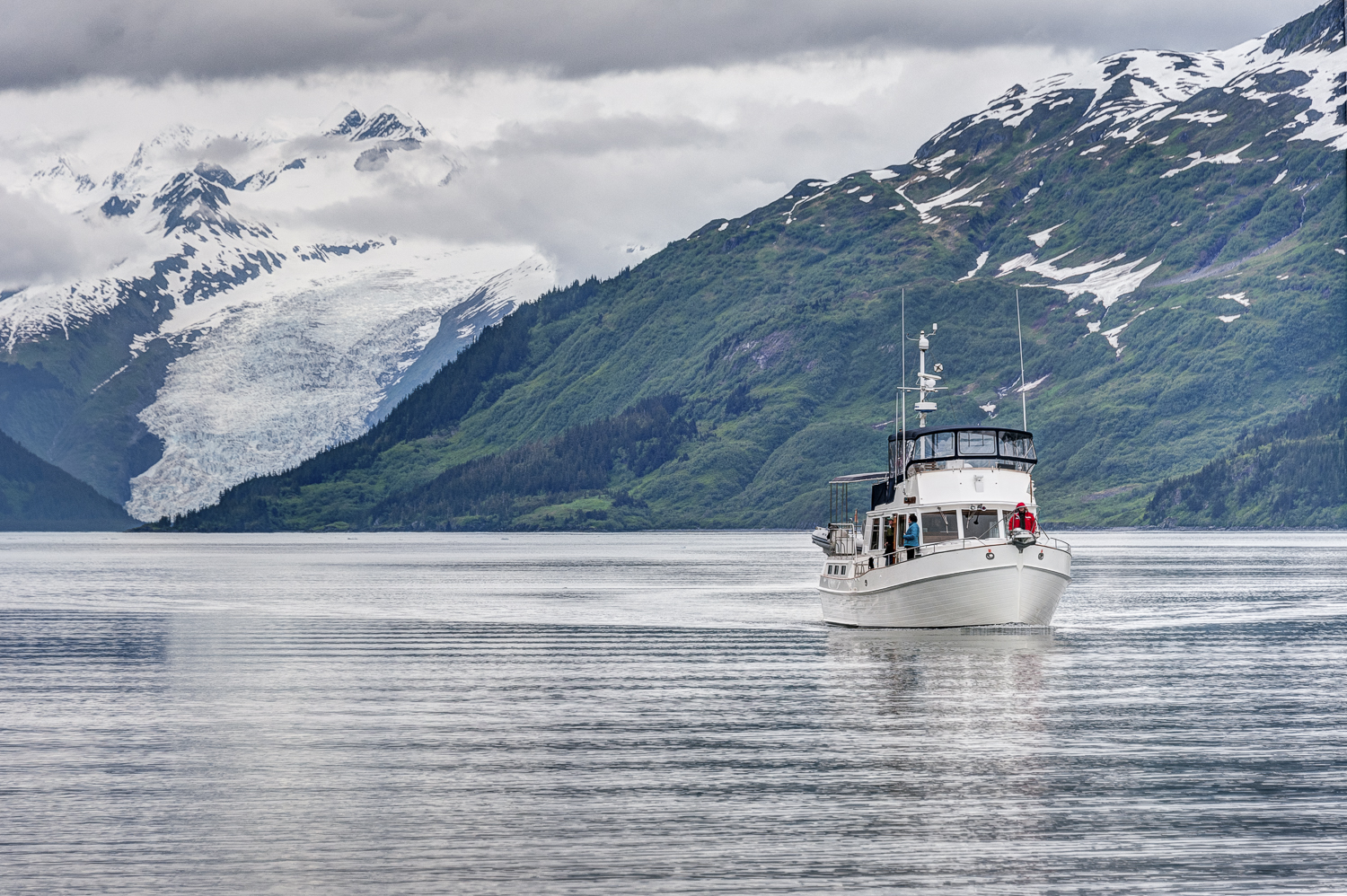 """Kathy Cox on the bow of her boat,  Telita , with the Coxe Glacier in the background. Only separated by one """"e""""."""