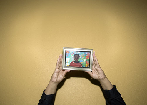 Wesaam Al-Badry,  Pam Saucer holds a photo of her son David Saucer II