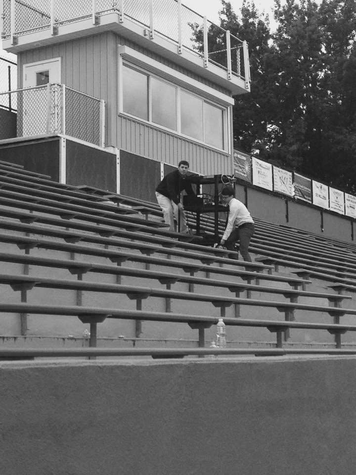 Josh (abeam) and I (astern) carrying a card of equipment up the bleachers.