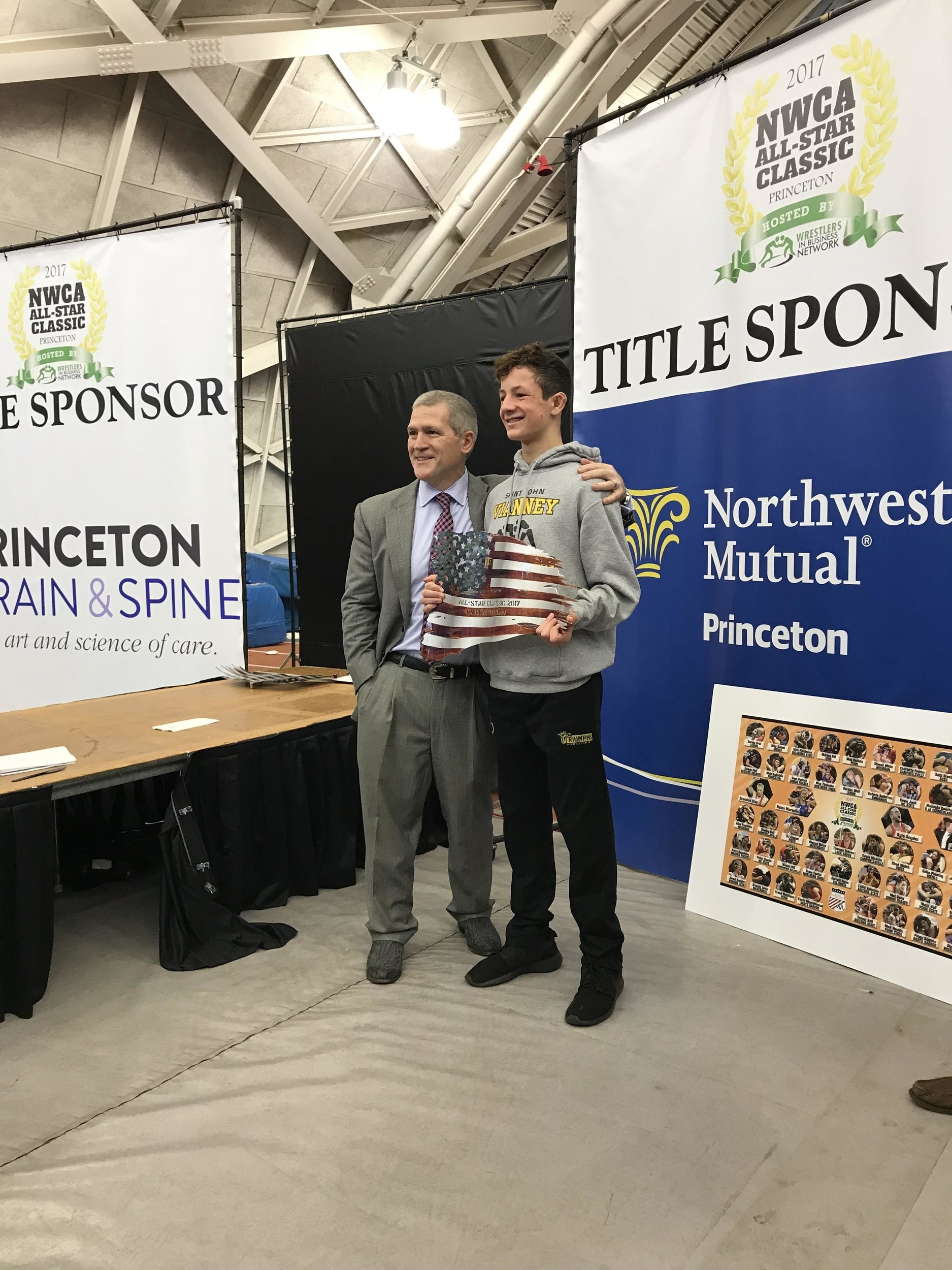 "WIMS founder, Joe Butler, with Dr. Mark McLaughlin receiving the ""Wrestle Back"" award at the 2017 NWCA All-Star classic presented by the Wrestlers in Business Network."
