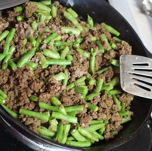 Saueteeing grass-fed beef with our garden organic green beans in a Lodge cast-iron skillet