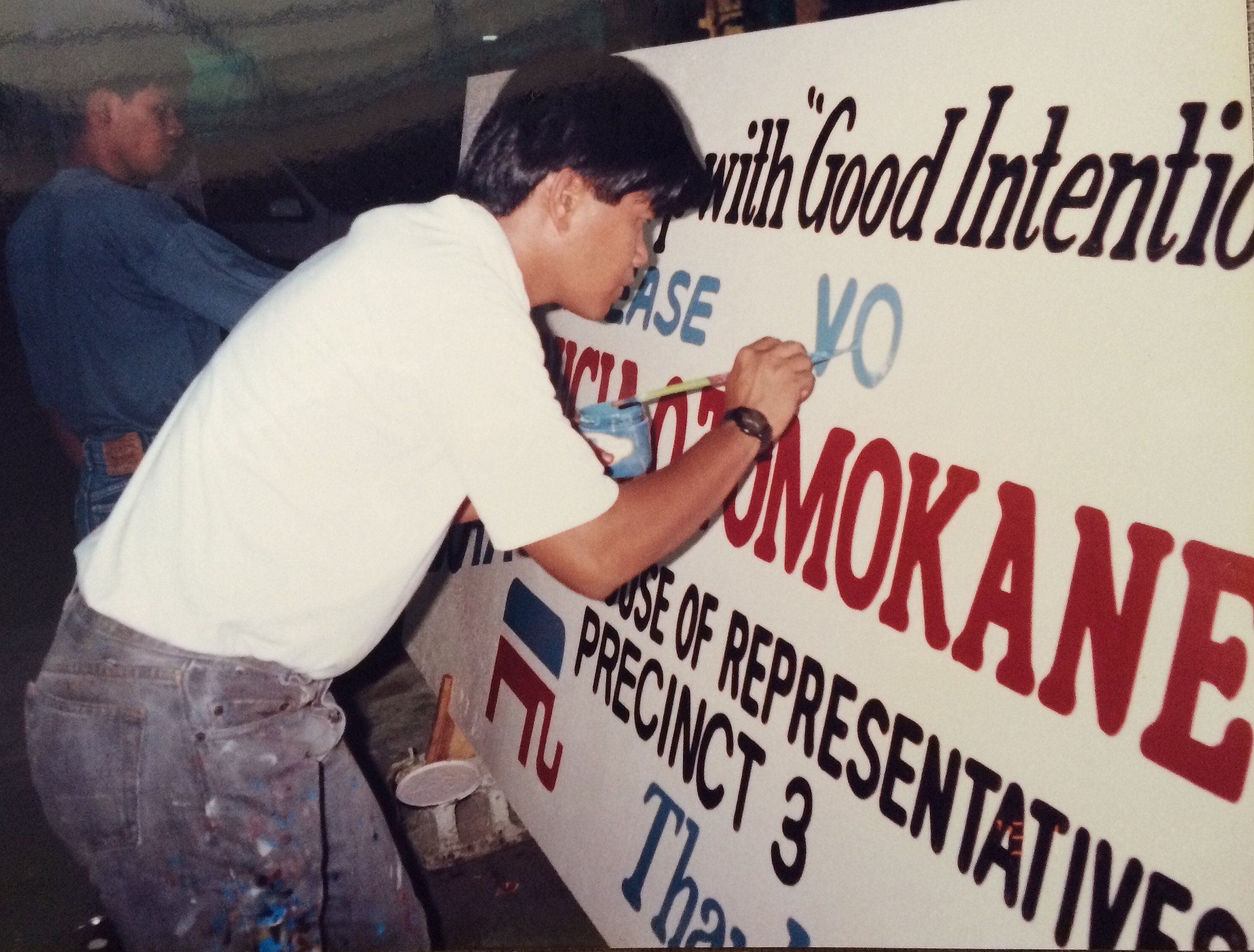 A man paints a wooden sign for Mom when she was running for House of Representatives for the Republican Party in Saipan