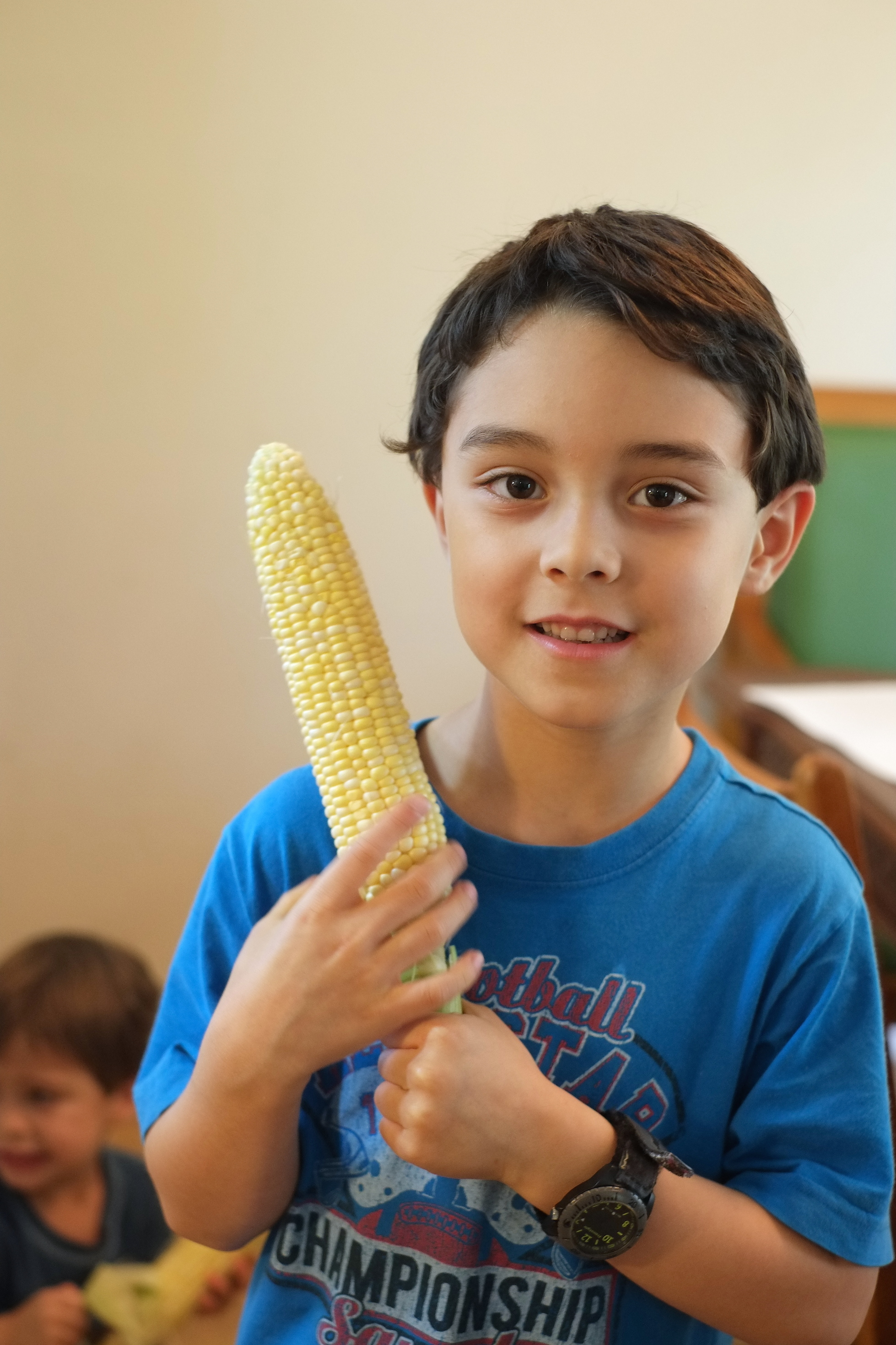 Abraham holding organic corn he was helping the family shuck