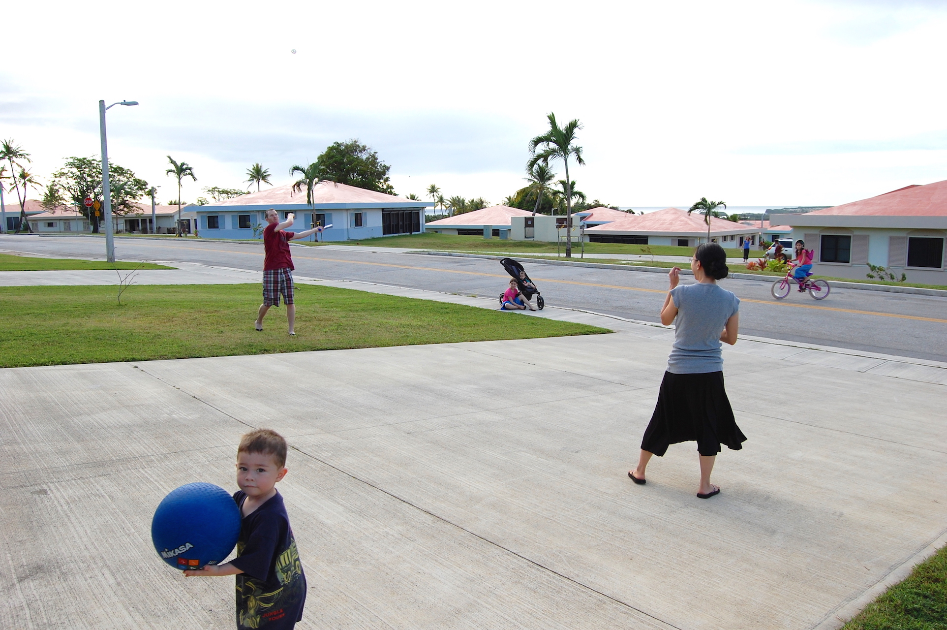 Tim and Franicia batting playing baseball with children Guam ocean view