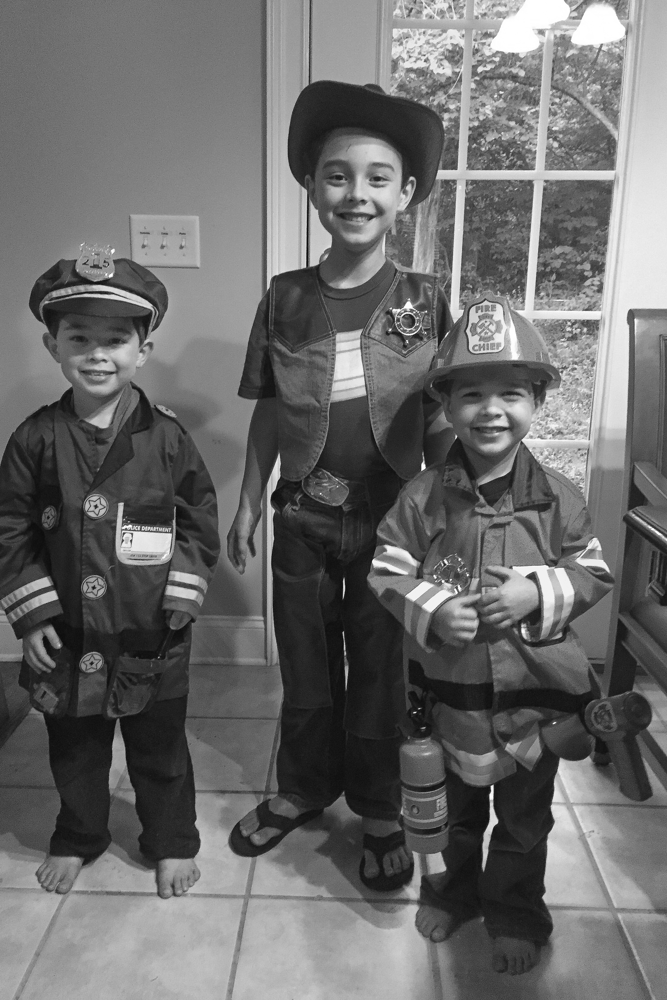 2015 - Noah (5), Abraham (7), and Daniel (3) are excited to use the new fireman, police, and cowboy outfits they bought with their own chore money.