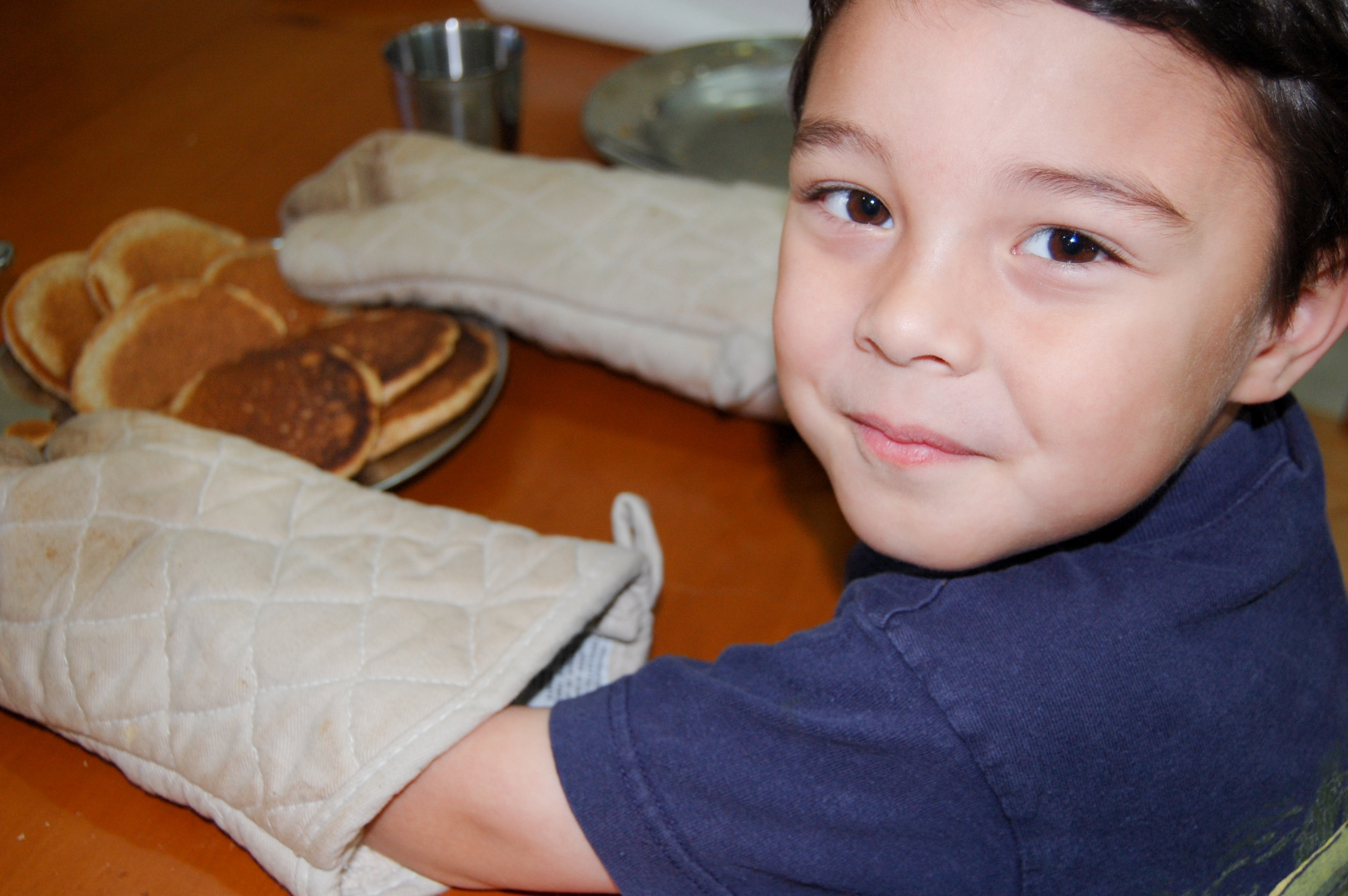 2012  - Abraham (4) serves homemade organic pancakes from the flour we milled with our mill. I believe I had him help me flip the miniature pancakes in our cast iron skillets.