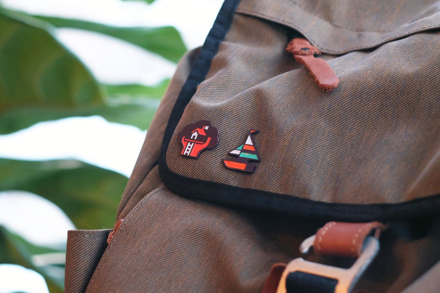 Treehouse and sailboat enamel pin design photograph on backpack by Matt Anderson / Canopy Design & Illustration.