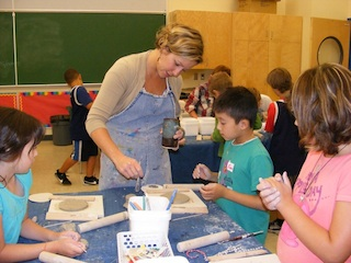 Renée helping kids create their images on their hand-made tiles for a future mural for their school.
