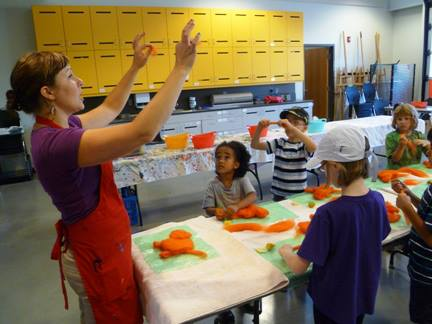 Renée teaching the kids how to layer the wool to create a wet-felted tiger!
