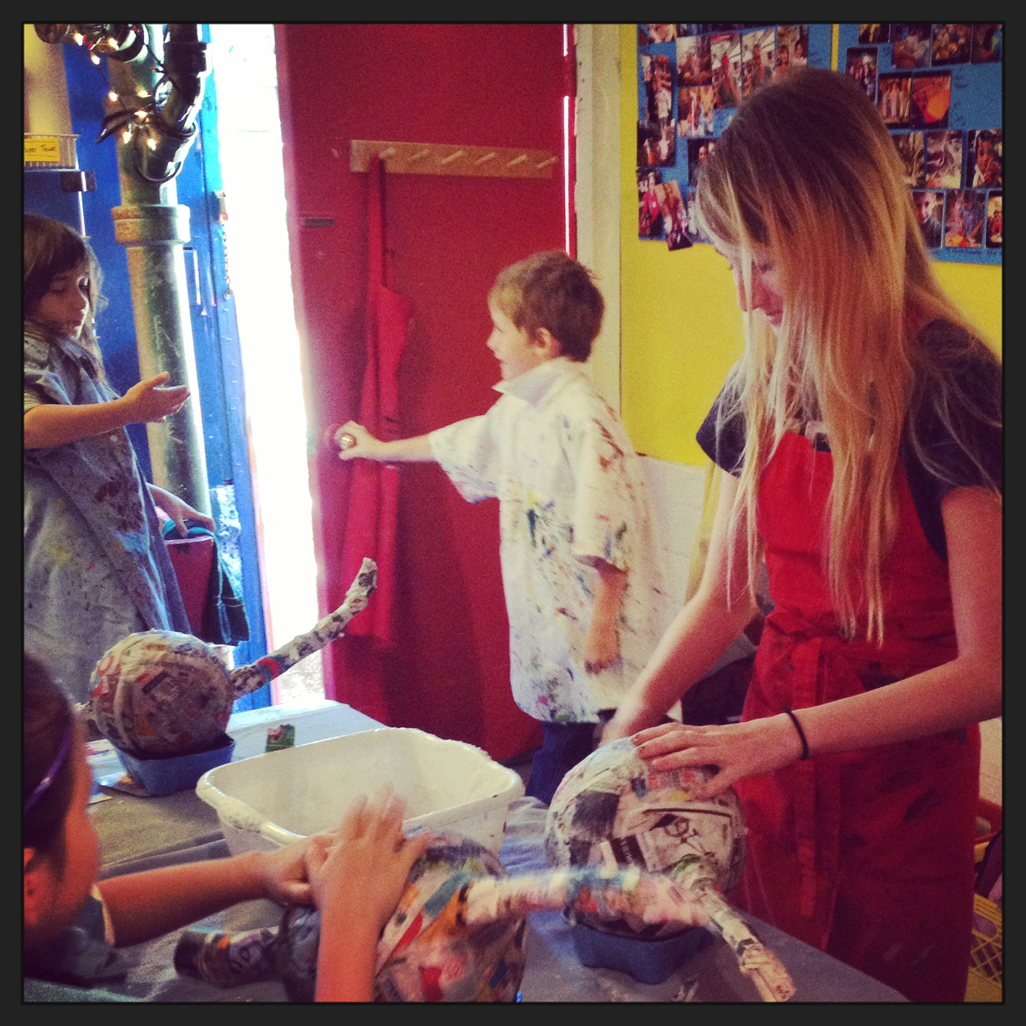 Shayden doing the final touches on a tired artist's paper maché dragon at a camp.