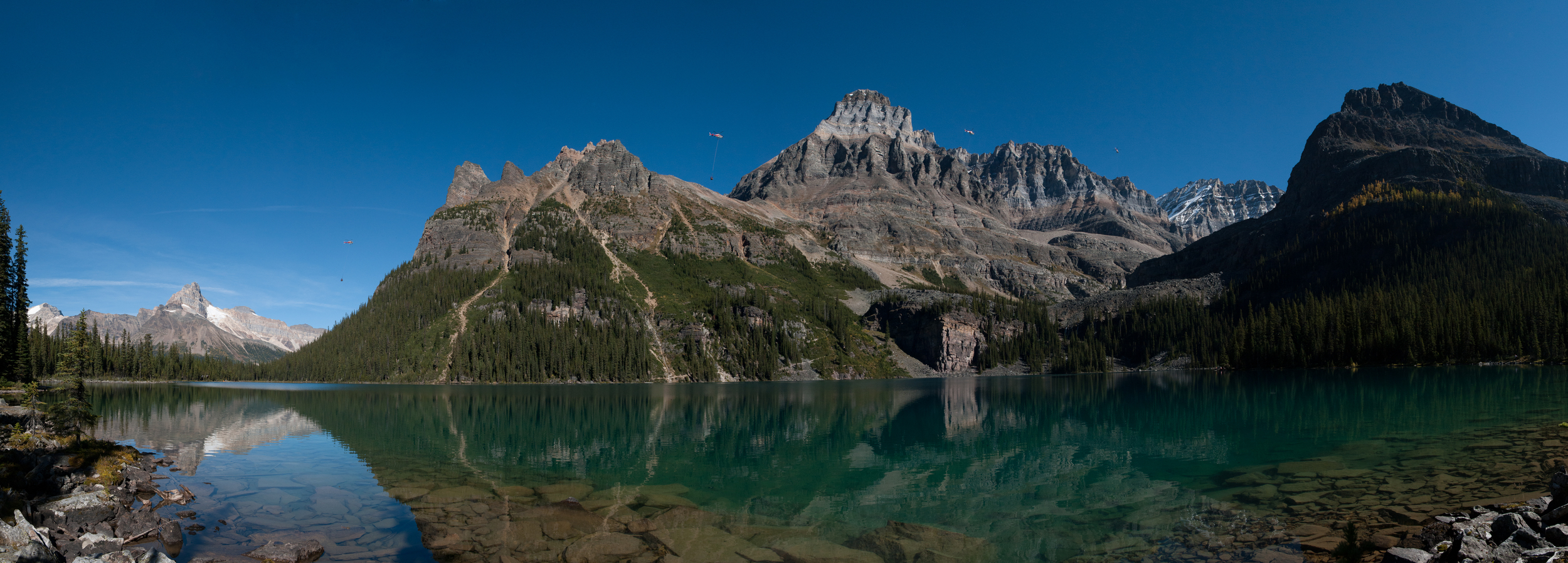 Panoramic photograph of Lake O'Hara capturing a helicopter at four different positions along it's flight to Abbot Pass Hut.