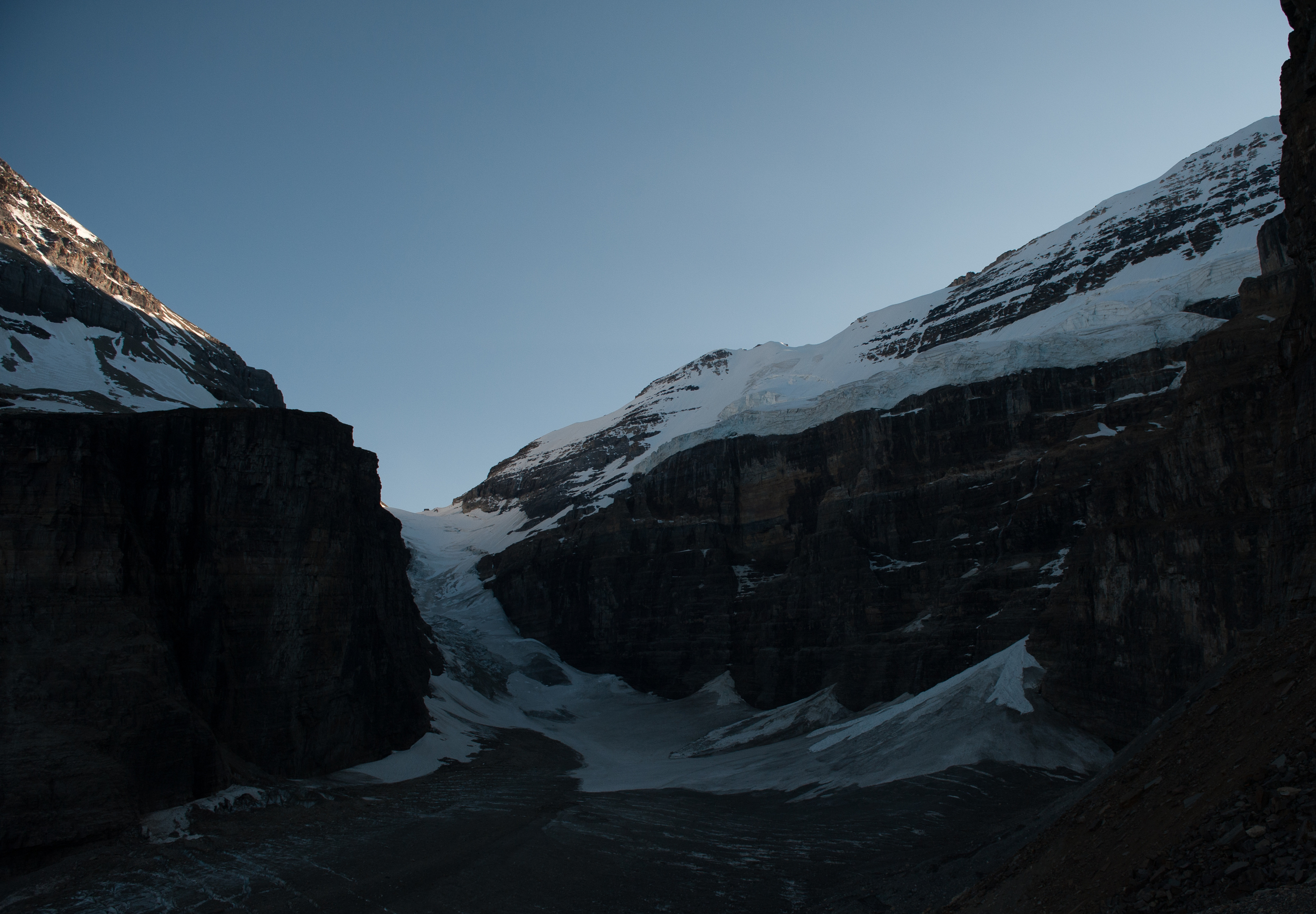 Abbot Hut as seen from the Plain of Six Glaciers. The hut is just visible above the low point of Abbot Pass it appears as a dark rectangle just above the snow. Victoria Glacier is on the right.