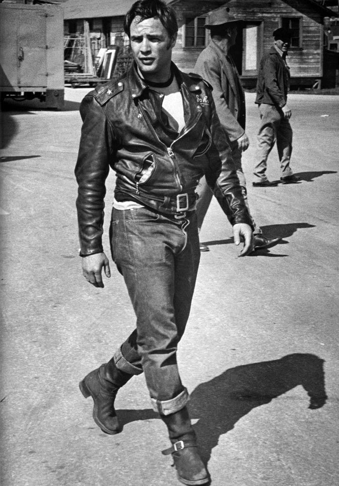 The quintessential Brando look from the set of  The Wild Ones - raw denim, boots, teeshirt, and leather jacket.