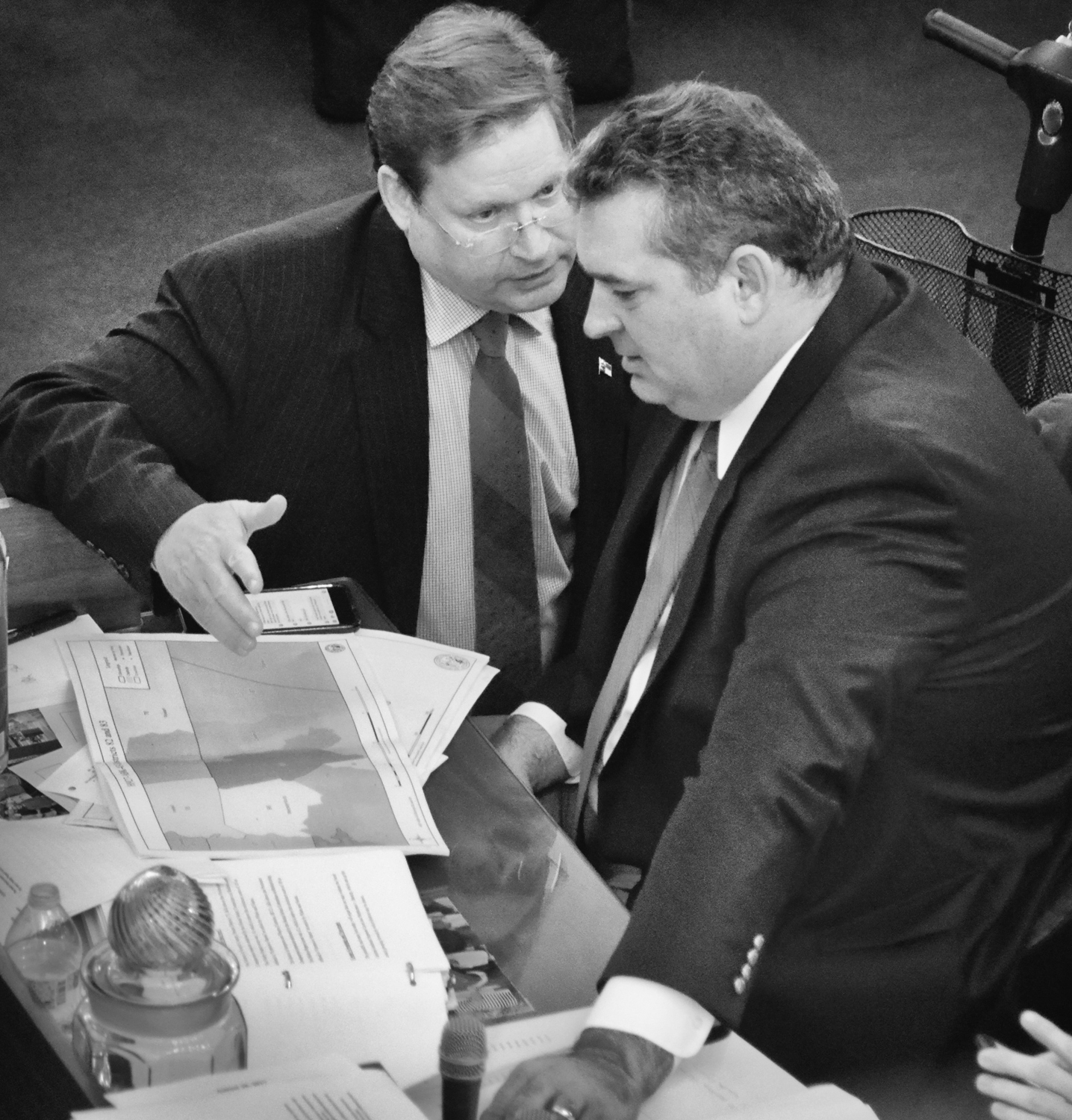 Rep. Nelson Dollar (left) and Rep. David Lewis confer on the floor of the House during debate prior to the vote.
