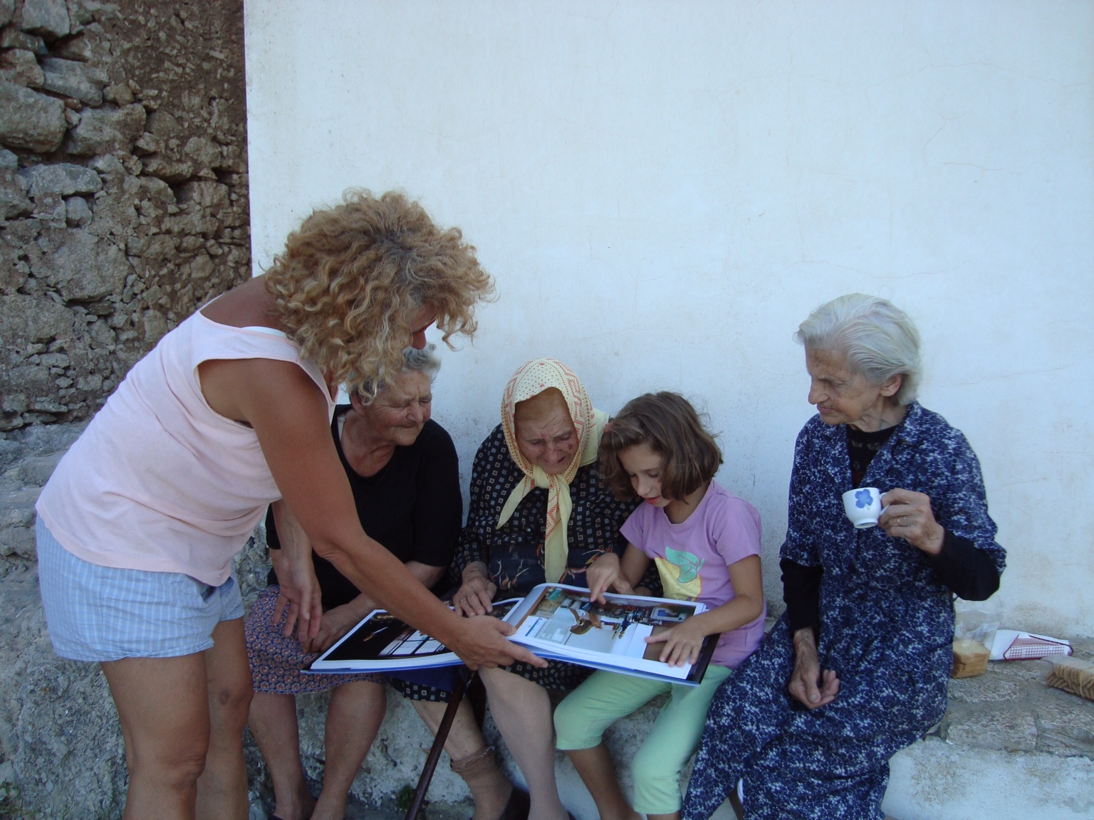 Theochari with some other women from the village paging through the book.