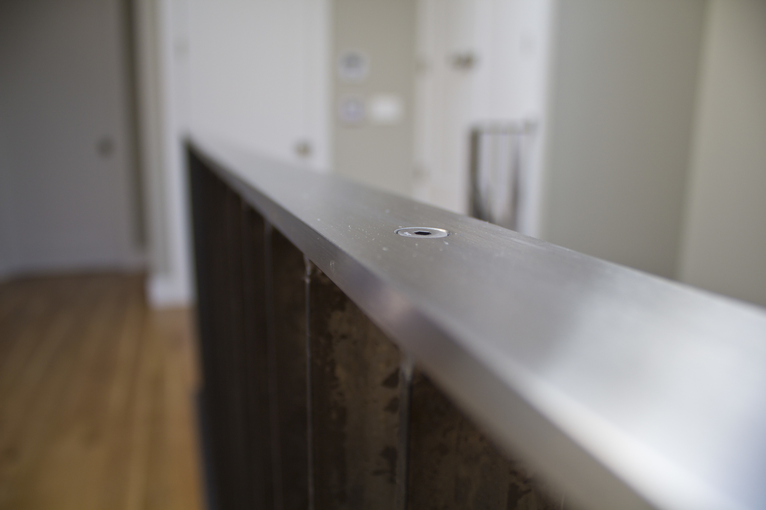 Guard rail in a remodeled San Francisco residence: polished stainless steel top rail mounted to a hot-rolled carbon steel picket weldment for aesthetic contrast.