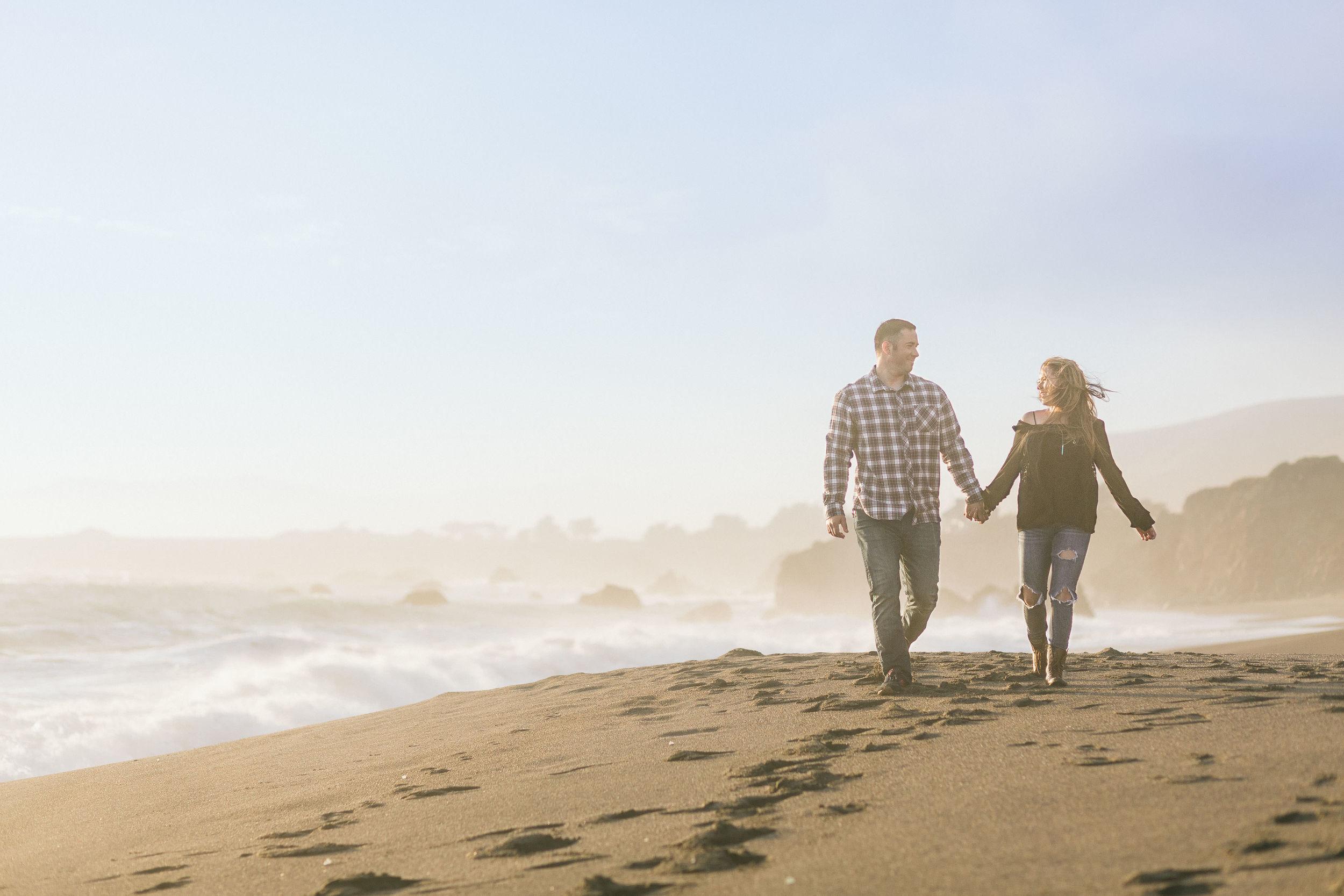 Couple-holding-hands-beach-sunset
