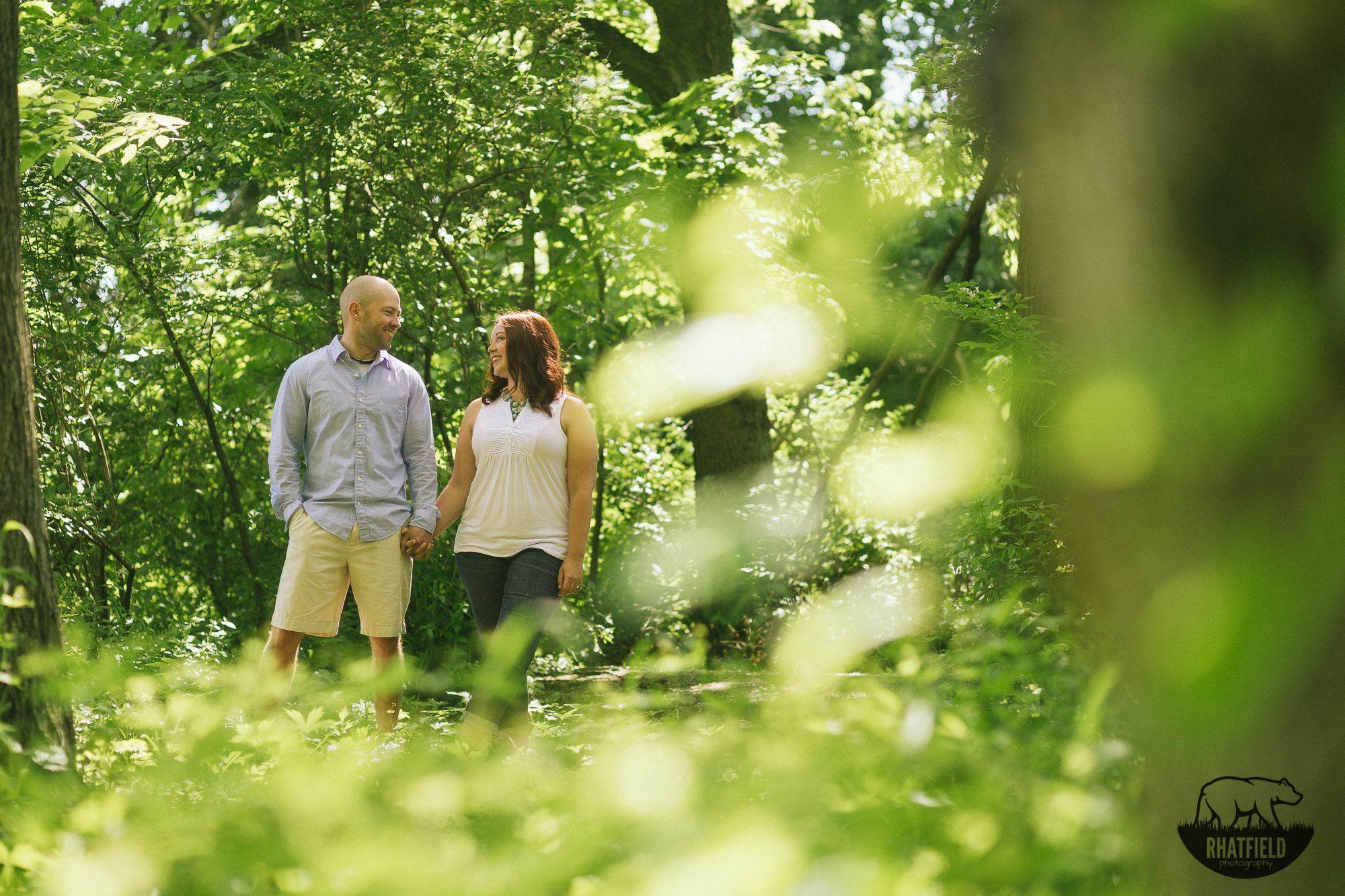 engaged-couple-looking-green-trees