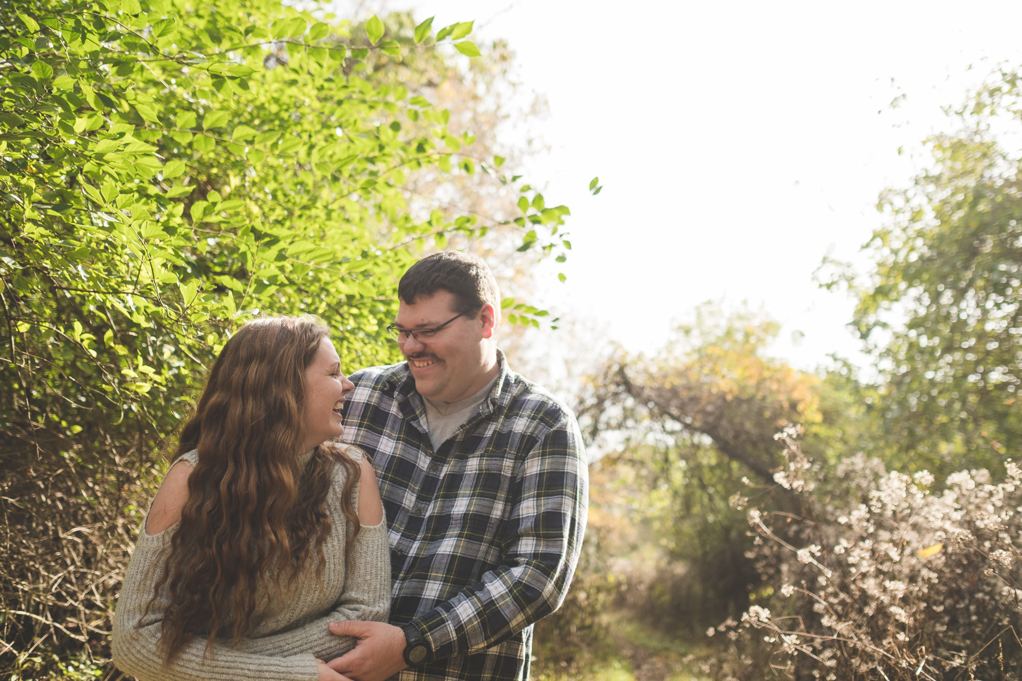 engaged-couple-laughing-together-on-nature-trail-in-fall